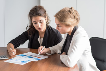 Business women working with diagrams