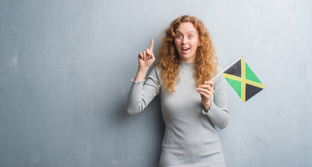 Young redhead woman over grey grunge wall holding flag of Jamaica surprised with an idea or question pointing finger with happy face, number one