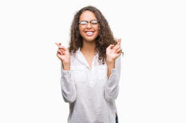 Beautiful young hispanic woman smiling crossing fingers with hope and eyes closed. Luck and superstitious concept.