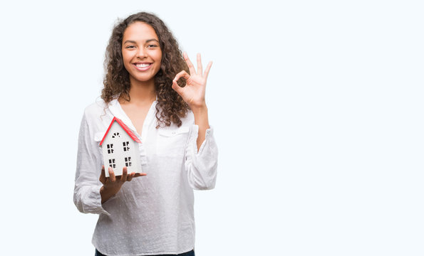 Young hispanic real state agent woman holding small house doing ok sign with fingers, excellent symbol