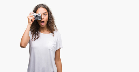Young hispanic woman taking pictures using vintage camera scared in shock with a surprise face, afraid and excited with fear expression