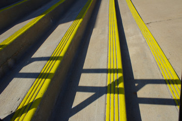 Bright Yellow Safety Lines Crossed With Zig Zag Grey Railing Shadows