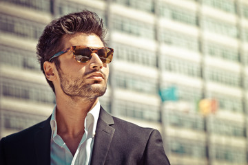 Handsome businessman with sunglasses, outdoor in the city. Charming and modern style, with shirt and suite. Cool hairstyle. Behind him a high-rise office building.