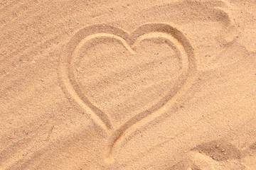 The heart is drawn on the sand. Beach background. Top view