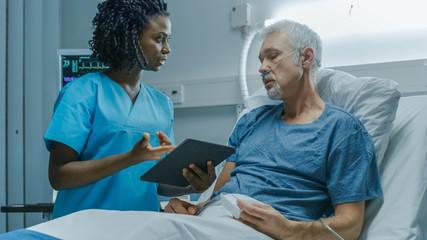 In the Hospital, Senior Patient Lying in the Bed Talking to a Nurse who is Holding Tablet Computer Showing Him Information. In the Technologically Advanced Hospital Ward.