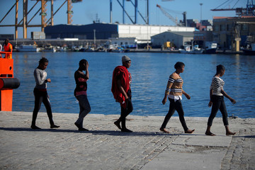 Migrant women walk after disembarking a rescue boat at the port of Malaga
