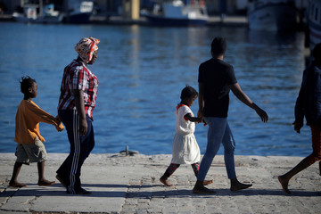 Migrants walk after disembarking a rescue boat at the port of Malaga