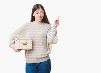 Young Chinese woman over isolated background holding a box very happy pointing with hand and finger to the side