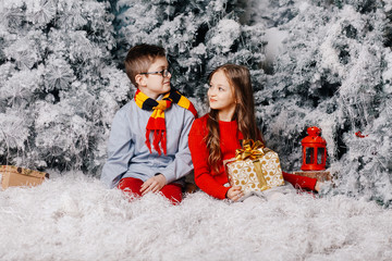 Brother and sister are sitting in the snow near the Christmas trees and holding a Christmas present