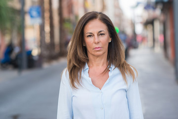 Beautiful middle age hispanic woman at the city street on a sunny day with a confident expression on smart face thinking serious