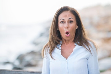 Beautiful middle age hispanic woman at the sea shore on a sunny day scared in shock with a surprise face, afraid and excited with fear expression