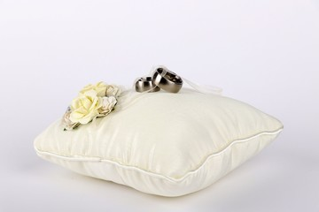 wedding rings - silver wedding rings on a white silk pillow
