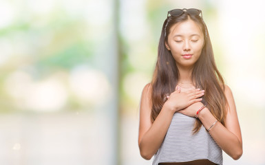 Young asian woman wearing sunglasses over isolated background smiling with hands on chest with closed eyes and grateful gesture on face. Health concept.