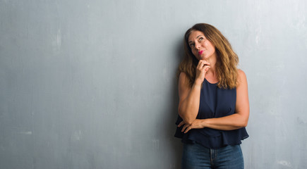 Middle age hispanic woman standing over grey grunge wall with hand on chin thinking about question, pensive expression. Smiling with thoughtful face. Doubt concept.
