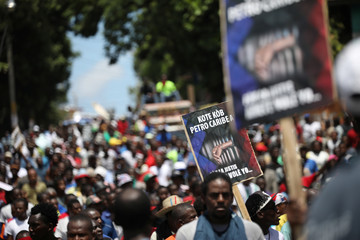 Protesters walk during a march to demand an investigation into the alleged misuse of Venezuela-sponsored PetroCaribe funds by previous administrations, in Port-au-Prince