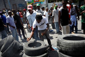 A man tries to light a barricade made with tires during a march to demand an investigation into the alleged misuse of Venezuela-sponsored PetroCaribe funds by previous administrations, in Port-au-Prince