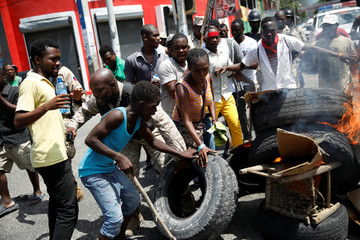 A Haitian National Police officer removes a tire from a barricade during a march to demand an investigation into the alleged misuse of Venezuela-sponsored PetroCaribe funds by previous administrations, in Port-au-Prince