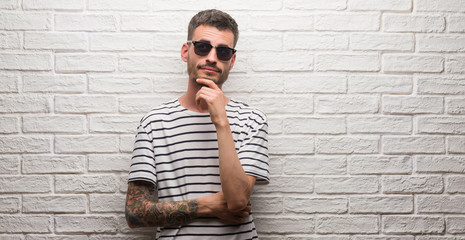 Young adult man wearing sunglasses standing over white brick wall with hand on chin thinking about question, pensive expression. Smiling with thoughtful face. Doubt concept.