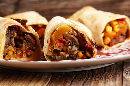 Burritos wraps with beef and vegetables on wooden background. Beef burrito, mexican food