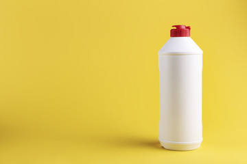 white plastic bottle with detergent without label on a yellow background. place for text.