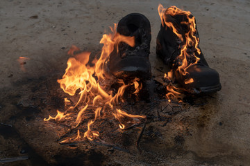 Black working boots made of thick pork skin burning in the fire. The concept of burning earth under the feet of enemies.