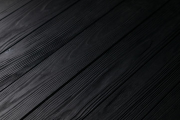 Black wooden background texture . View at an angle