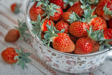 Ripe strawberries in a pot on the table.