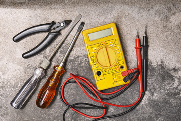 DIY home electricity working tools, screwdrivers, pliers and multimeter on cement background