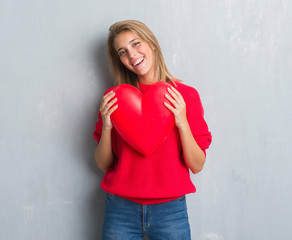 Beautiful young woman over grunge grey wall holding red heart with a happy face standing and smiling with a confident smile showing teeth