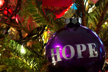 A purple bulb Christmas ornament hanging on a Christmas tree with HOPE in silver etched on it.