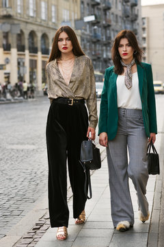 Outdoor full body portrait of two young beautiful fashionable women wearing stylish trendy clothes, shoes and accessories walking in street of european city. Street fashion concept