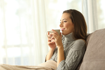 Woman enjoying a cup of coffee in winter at home