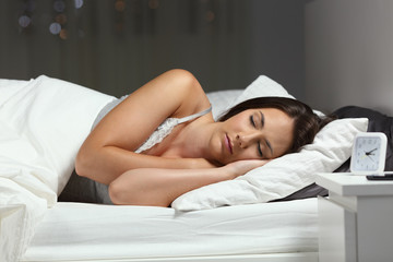 Woman sleeping deeply in a bed in the night