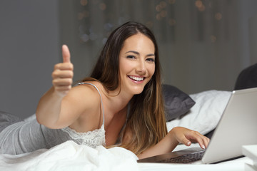 Woman using a laptop on the bed with thumbs up