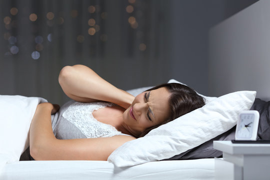 Woman suffering fibromyalgia in the night in the bed