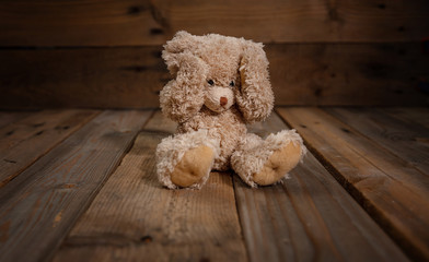Child abuse.Teddy bear covering eyes, dark empty background, copy space