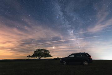 ein Geländewagen SUV unter Sternenhimmel und Milchstraße