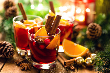 Christmas mulled red wine with spices and oranges on a wooden rustic table. Traditional hot drink at Christmas