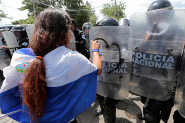 A demonstrator sprays on the shield of a riot police during a protest against Nicaraguan President Daniel Ortega's government in Managua