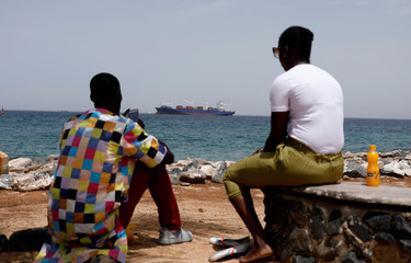 A container ship is seen offshore as a Senegalese couple sits on the island of Goree off the coast of Dakar