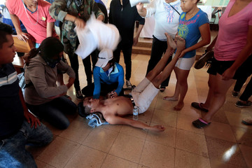 Demonstrators help an injured protester during a protest against Nicaraguan President Daniel Ortega's government in Managua