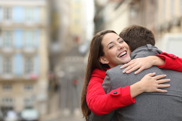 Cheerful couple meeting and hugging in the street