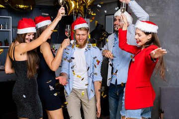 Celebrating New Year together. Group of beautiful young people in Santa hats throwing colorful confetti and looking happy.
