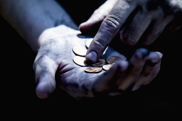 Hand of beggar with some coins begging for money (poverty, hunger, anxiety, bankrupt concept)