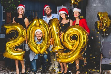Celebrating New Year party. Group of cheerful young girls in beautiful wearing carrying gold colored numbers 2019 and throwing confetti.