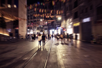 Blurry motion image of people walking in Istiklal Avenue (the city's main pedestrian boulevard) at night in Istanbul. The street which is lined with 19th-century buildings, shopping chains and cafes.