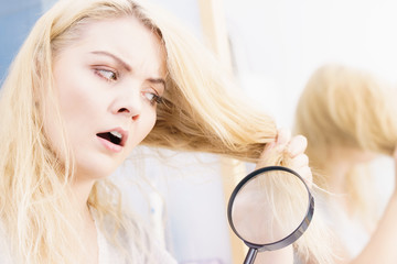Woman magnifying her split ends hair