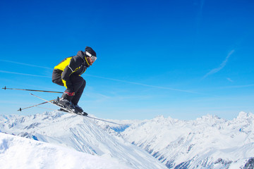 Jumping skier at mountains