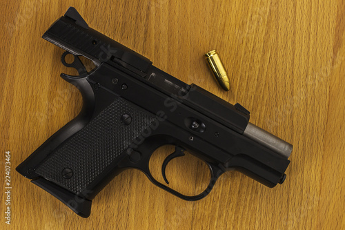Subcompact 9mm pistols, very small gun with bullet on wood