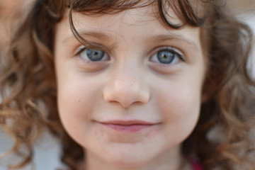 Closeup portrait of curly haired toddler with striking, huge blue eyes